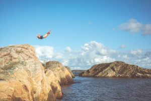 man diving from cliff above ocean
